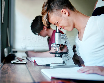 Buy stock photo Cropped shot of a focused young student looking through a microscope while being seated at his desk at school