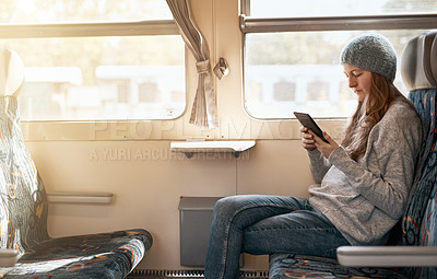 Buy stock photo Cropped shot of an attractive young woman using her tablet while sitting on a train