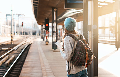 Buy stock photo Rearview shot of an unrecognizable young woman waiting for a train at the station
