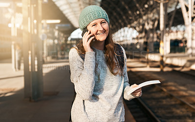 Buy stock photo Cropped shot of an attractive young woman making a phonecall while waiting for a train