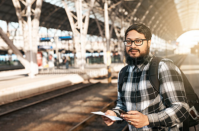Buy stock photo Cropped shot of a handsome young man sending text messages while waiting for a train
