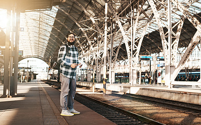 Buy stock photo Full length shot of a handsome young man sending text messages while waiting for a train