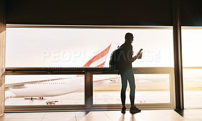 Buy stock photo Rearview shot of a young woman using her cellphone at the airport