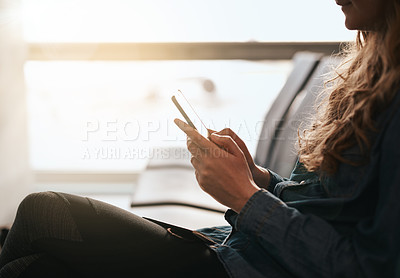 Buy stock photo Cropped shot of a young woman using her cellphone while waiting at the airport