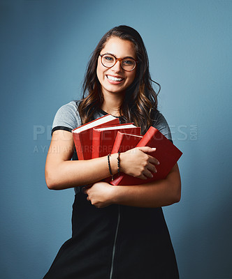 Buy stock photo Studio portrait of an attractive young woman holding a pile books against a blue background