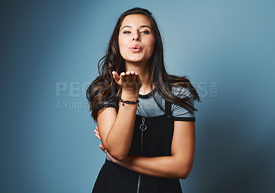 Buy stock photo Studio portrait of an attractive young woman blowing a kiss against a blue background