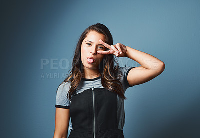 Buy stock photo Studio portrait of an attractive young woman sticking out her tongue against a blue background