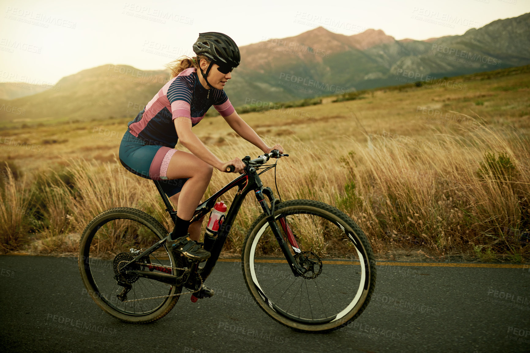 Buy stock photo Shot of a woman riding a bicycle out in the countryside