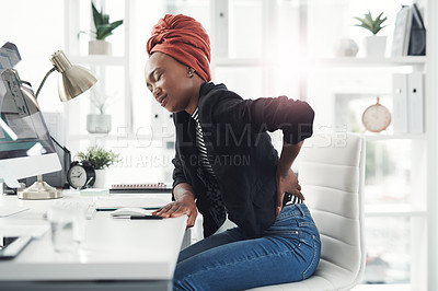 Buy stock photo Cropped shot of an attractive young businesswoman holding her back in pain while sitting at her desk in the office
