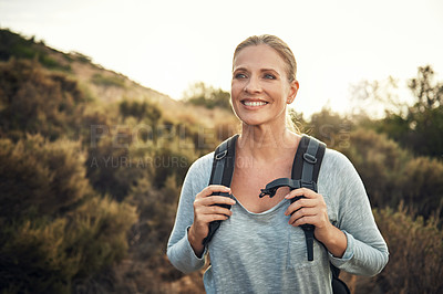 Buy stock photo Shot of a mature woman hiking through the mountains