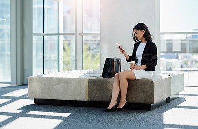 Buy stock photo Full length shot of an attractive young businesswoman using her smartphone in her workplace