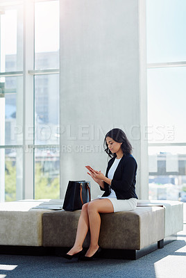 Buy stock photo Full length shot of an attractive young businesswoman using her smartphone in a waiting room