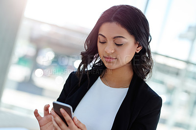 Buy stock photo Cropped shot of an attractive young businesswoman using her smartphone in an office