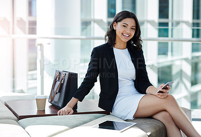 Buy stock photo Cropped portrait of an attractive young businesswoman using her smartphone in her office