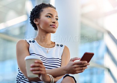 Buy stock photo Cropped shot of an attractive young woman using her smartphone in the workplace