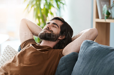 Buy stock photo Shot of a handsome young man relaxing on a sofa in his living room