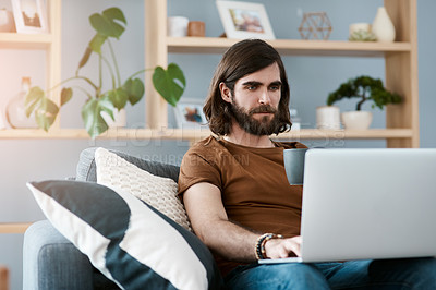 Buy stock photo Shot of a handsome young man using his laptop while relaxing on a sofa in his living room