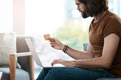 Buy stock photo Shot of a handsome young man holding a credit card and using his laptop while relaxing in his living room