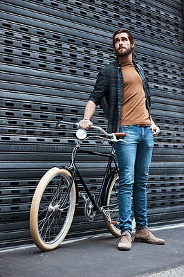 Buy stock photo Full length shot of a handsome young man posing next to his bicycle outdoors