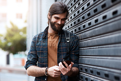 Buy stock photo Shot of a handsome young man using his cellphone while walking in the city