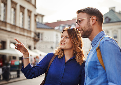 Buy stock photo Shot of a young couple sightseeing in a foreign city