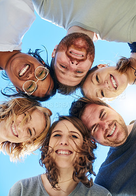 Buy stock photo Low angle shot of a group of friends huddled together