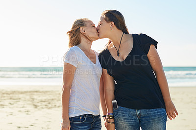 Buy stock photo Cropped shot of a loving couple spending the day at the beach