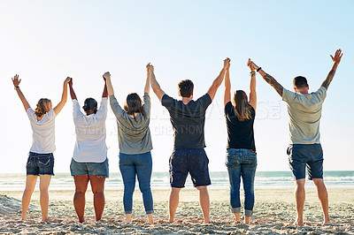 Buy stock photo Rearview shot of a group of friends standing with their arms raised at the beach