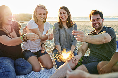 Buy stock photo Shot of a group of friends holding sparklers while spending time on the beach