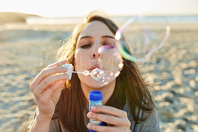 Buy stock photo Cropped shot of a young woman blowing bubbles on the beach