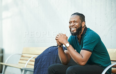 Buy stock photo Shot of a cheerful young man sitting on a bench outdoors
