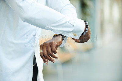 Buy stock photo Shot of an unrecognzibale businessman cuffing his shirt outdoors