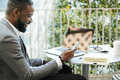 Buy stock photo Shot of a handsome young businessman using his cellphone while relaxing outdoors