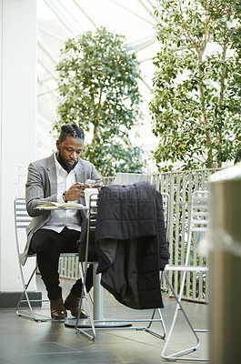 Buy stock photo Full length shot of a handsome young businessman using his cellphone while relaxing outdoors