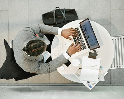 Buy stock photo High angle shot of a handsome young businessman sitting in a desk and working on his laptop