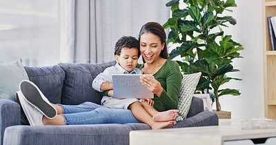 Buy stock photo Full length shot of an attractive young woman and her son using a digital tablet in their living room