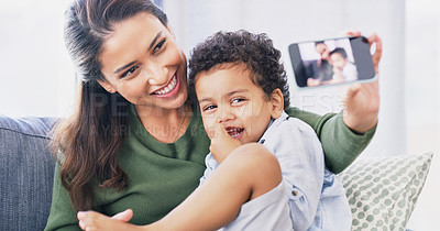 Buy stock photo Cropped shot of an attractive young woman and her son taking selfies in their living room