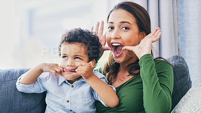 Buy stock photo Cropped portrait of an attractive young woman and her son pulling faces in their living room