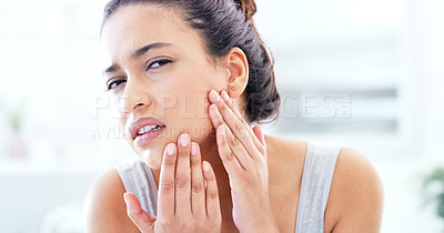 Buy stock photo Shot of a young woman looking unhappy while looking at her skin