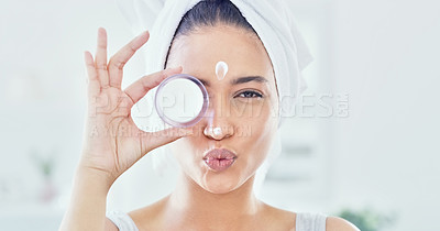 Buy stock photo Cropped shot of an attractive young woman applying moisturizer to her face