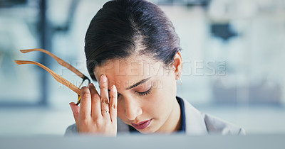 Buy stock photo Cropped shot of a stressed young businesswoman working on a computer and suffering from a headache inside the office