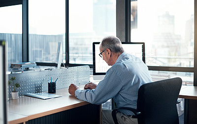 Buy stock photo Rearview shot of a mature businessman working at his desk
