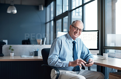 Buy stock photo Cropped shot of a mature businessman using his cellphone at the office