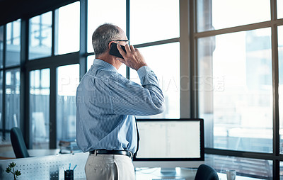 Buy stock photo Shot of a mature businessman talking on his cellphone in an office
