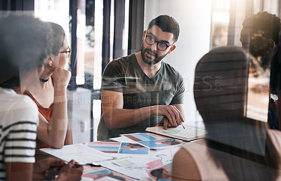 Buy stock photo Shot of a young designer having a meeting with his colleagues in an office