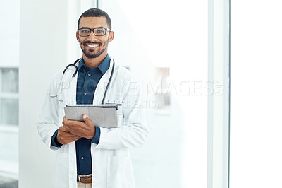 Buy stock photo Portrait of a young doctor holding a digital tablet in a modern hospital