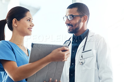 Buy stock photo Shot of two young doctors using a digital tablet in a modern hospital