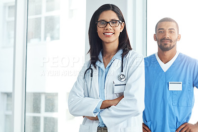 Buy stock photo Portrait of two confident young doctors working in a modern hospital