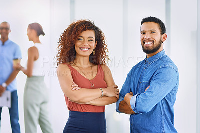 Buy stock photo Portrait of two young businesspeople standing in an office with their colleagues in the background
