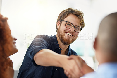 Buy stock photo Cropped shot of two young businessmen shaking hands after a successful deal in the office